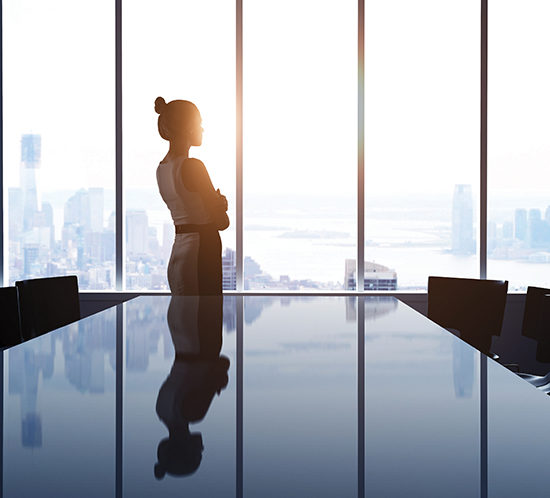 A businesswoman looking out the window of her office - Lagentium Insurance Brokers