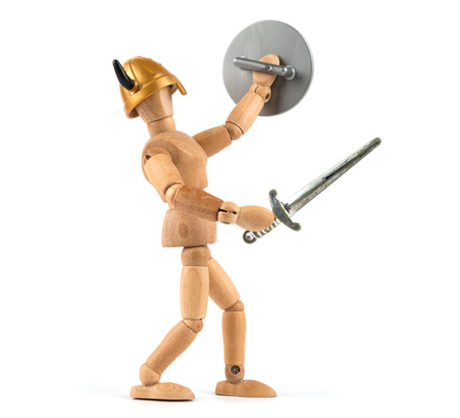 A wooden model of a man with a sword and shield