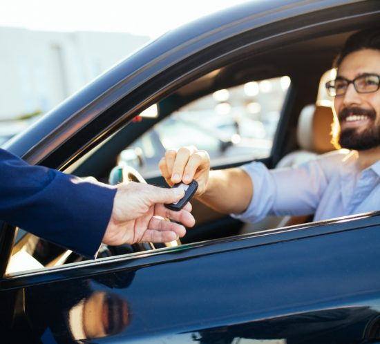 Young handsome businessman buying car