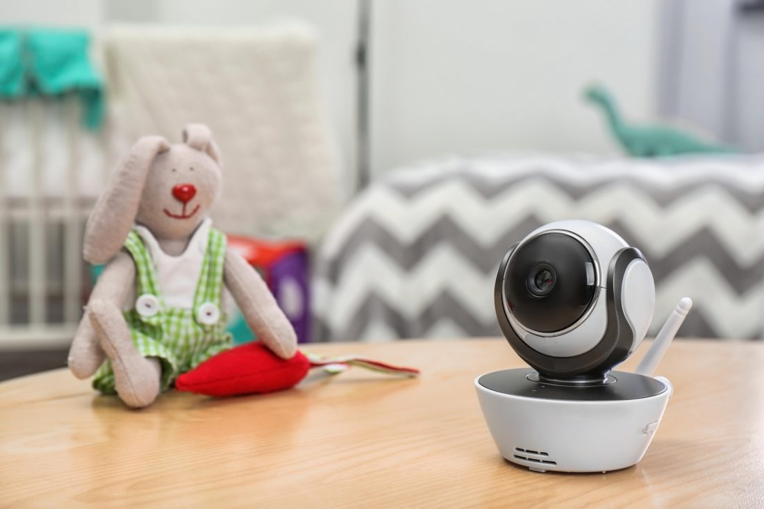 Baby monitor and toy on table in room, space for text. CCTV equipment